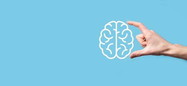 Męskiej ręki trzymającej ikonę mózgu