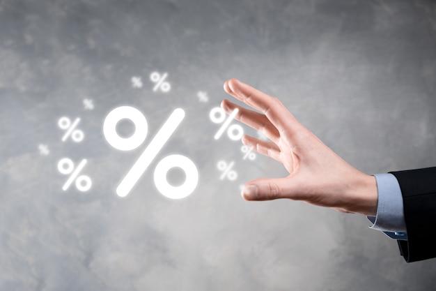 Męskiej ręki trzymającej ikonę procentu stopy procentowej na niebieskim tle. oprocentowanie finansowe i hipoteczne