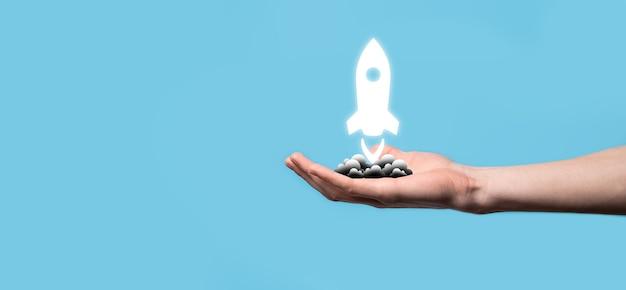 Męskiej ręki trzymającej ikonę rakiety, która startuje, uruchamia się na niebieskim tle. rakieta jest uruchamianie i wylatuje, rozpoczęcie działalności gospodarczej, ikona marketingu na nowoczesnym interfejsie wirtualnym. koncepcja uruchomienia.