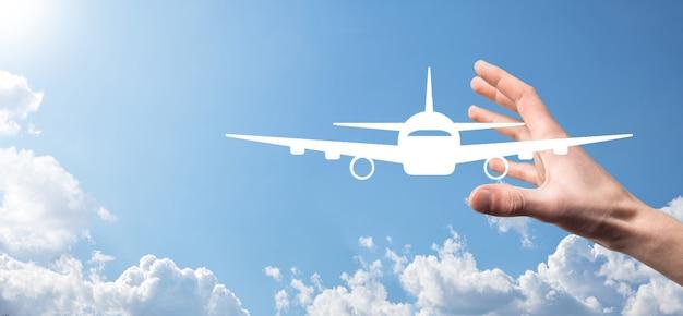 Męskiej ręki trzymającej ikonę samolot samolot na niebieskim tle. zakup biletu banner.nline. ikony podróży dotyczące planowania podróży, transportu, hotelu, lotu i paszportu. koncepcja rezerwacji biletów lotniczych.