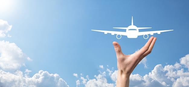 Męskiej ręki trzymającej ikonę samolot samolot na niebieskim tle. zakup biletu banner.nline. ikony podróży o planowanie podróży, transport, hotel, lot i paszport. koncepcja rezerwacji biletów lotniczych.