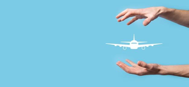 Męskiej ręki trzymającej ikonę samolotu samolotu na niebieskim tle. banner. zakup biletu online. ikony podróży dotyczące planowania podróży, transportu, hotelu, lotu i paszportu. koncepcja rezerwacji biletu lotniczego.