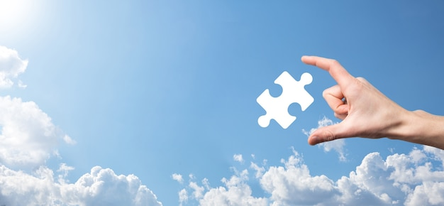 Męskiej ręki trzymającej ikonę układanki na niebieskim tle. utwory reprezentujące połączenie dwóch spółek lub joint venture, partnerstwo, koncepcję fuzji i przejęć.