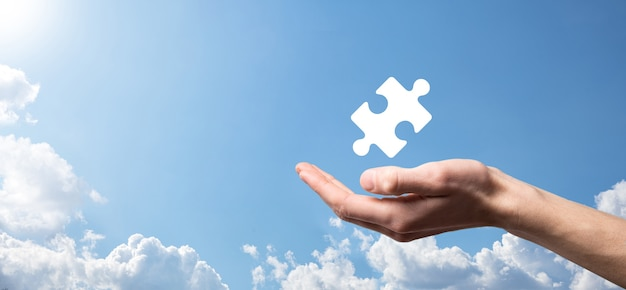 Męskiej ręki trzymającej ikonę układanki na niebieskim tle. utwory reprezentujące połączenie dwóch spółek lub joint venture, spółkę, koncepcję fuzji i przejęć.