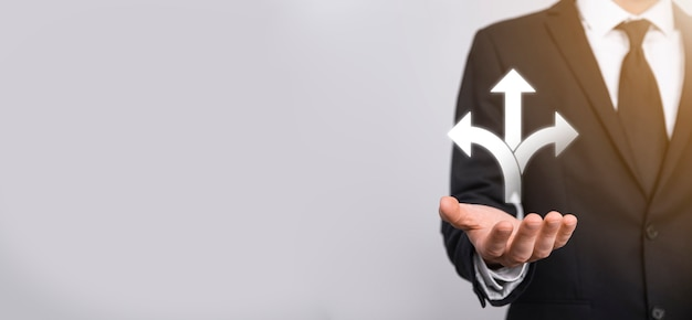 Męskiej ręki trzymającej ikonę z ikoną trzech kierunków na ciemnym tle. wątpliwości, mając do wyboru trzy różne opcje wskazane przez strzałki skierowane w przeciwnym kierunku koncepcji. sposoby
