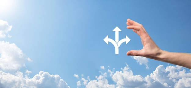 Męskiej ręki trzymającej ikonę z ikoną trzech kierunków na niebieskim tle. wątpliwości, mając do wyboru trzy różne opcje wskazane przez strzałki skierowane w przeciwnym kierunku koncepcji. sposoby