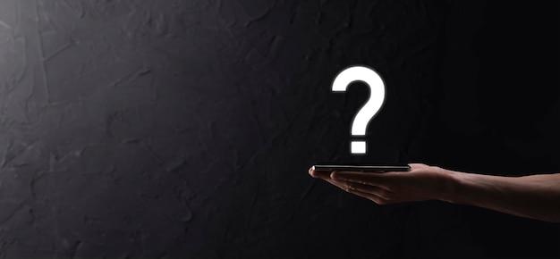Męskiej ręki trzymającej ikonę znaku zapytania na ciemnym tle. baner z miejsca kopii. miejsce na tekst.