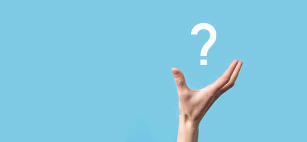 Męskiej ręki trzymającej ikonę znaku zapytania na niebieskiej powierzchni