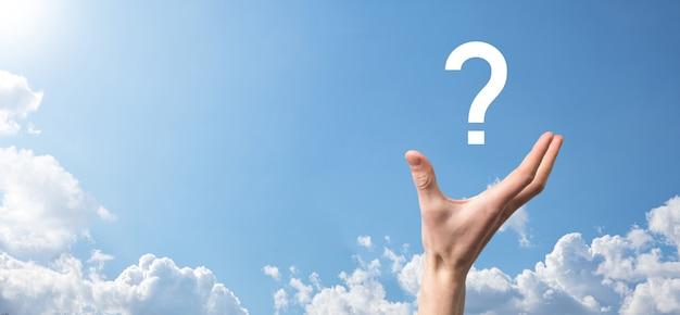 Męskiej ręki trzymającej ikonę znaku zapytania na niebieskim tle. baner z miejsca kopiowania. miejsce na tekst.
