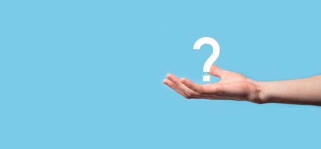 Męskiej ręki trzymającej ikonę znaku zapytania na niebieskim tle. baner z miejsca na kopię. miejsce na tekst.