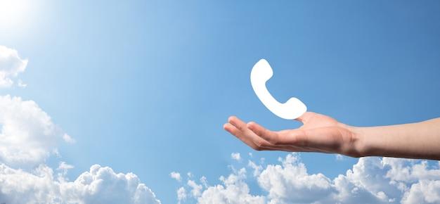 Męskiej ręki trzymającej inteligentny telefon komórkowy z ikoną telefonu. zadzwoń teraz komunikacja biznesowa centrum obsługi klienta koncepcja technologii obsługi klienta.
