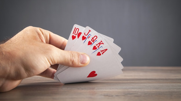 Męskiej ręki trzymającej karty do gry.