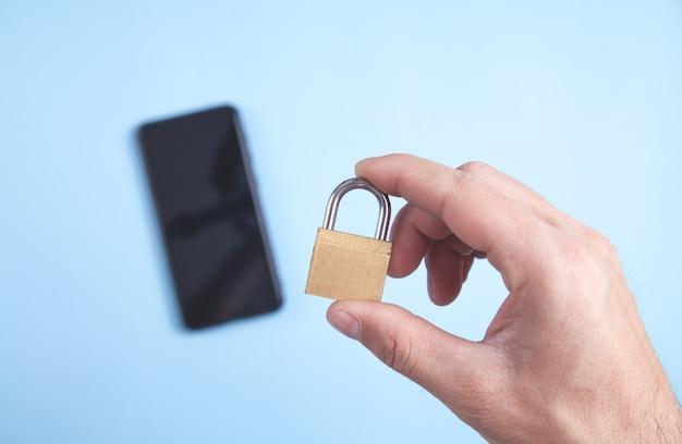 Męskiej ręki trzymającej kłódkę. koncepcja bezpieczeństwa smartfona