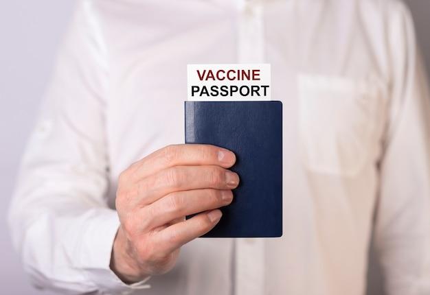 Męskiej ręki trzymającej lub pokazując paszport szczepionki