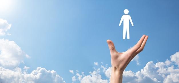 Męskiej ręki trzymającej ludzką ikonę na niebieskim tle. zarządzanie zasobami ludzkimi hr rekrutacja zatrudnienia headhunting concept.select koncepcja lidera zespołu. męskiej ręki kliknij ikonę człowieka. baner, skopiuj spase.