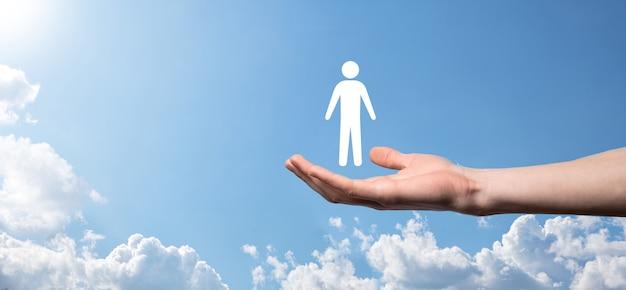 Męskiej ręki trzymającej ludzką ikonę na niebieskim tle. zarządzanie zasobami ludzkimi hr rekrutacja zatrudnienia headhunting concept.select koncepcja lidera zespołu. mężczyzna ręka kliknij ikonę człowieka. baner, skopiuj spase.