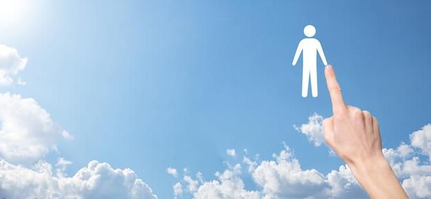 Męskiej ręki trzymającej ludzką ikonę na niebieskim tle. zasoby ludzkie zarządzanie zasobami ludzkimi rekrutacja