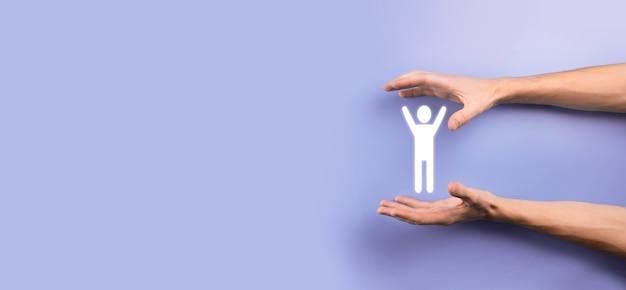 Męskiej ręki trzymającej ludzką ikonę na szarym tle. zarządzanie zasobami ludzkimi hr rekrutacja zatrudnienia headhunting concept.select koncepcja lidera zespołu. męskiej ręki kliknij ikonę człowieka. baner, skopiuj spase.