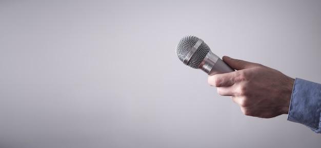 Męskiej ręki trzymającej mikrofon na szarym tle.