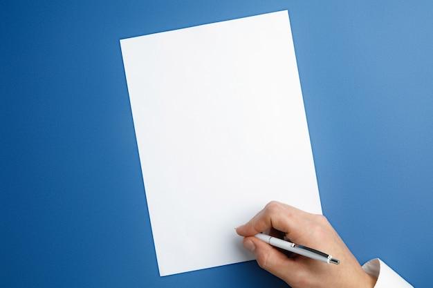 Męskiej ręki trzymającej pióro i pisania na pustym arkuszu na niebieskiej ścianie tekstu lub projektu. puste szablony do kontaktu, reklamy lub wykorzystania w biznesie. finanse, biuro, zakupy. copyspace.