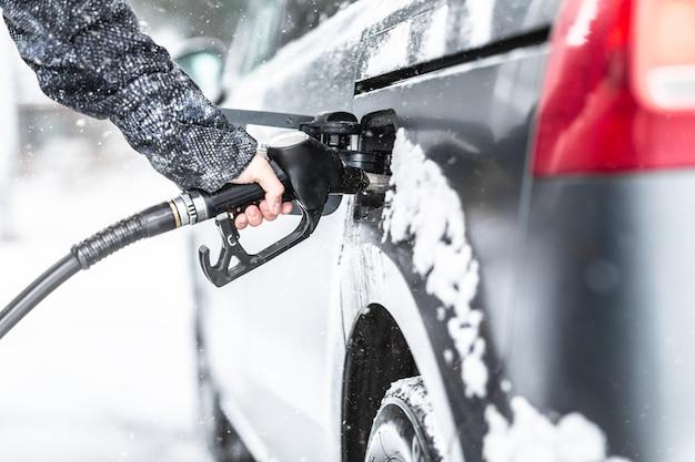 Męskiej ręki trzymającej pistolet paliwa podczas uzupełniania benzyny w jego minivan w mroźną zimę.