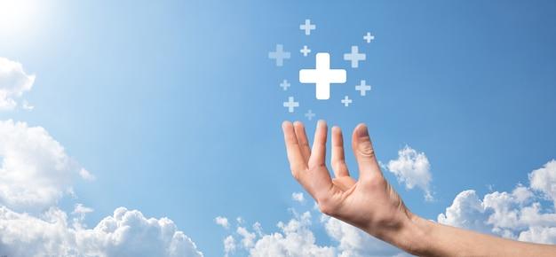 Męskiej ręki trzymającej plus ikona na niebieskim tle. wirtualny znak plus oznacza oferowanie pozytywnych rzeczy, takich jak korzyści, rozwój osobisty, zysk w sieci społecznościowej, ubezpieczenie zdrowotne, koncepcje rozwoju.