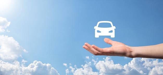 Męskiej ręki trzymającej samochód auto ikona na niebieskim tle. szeroka kompozycja banerowa.koncepcje ubezpieczenia samochodu i zrzeczenia się odszkodowań w razie kolizji