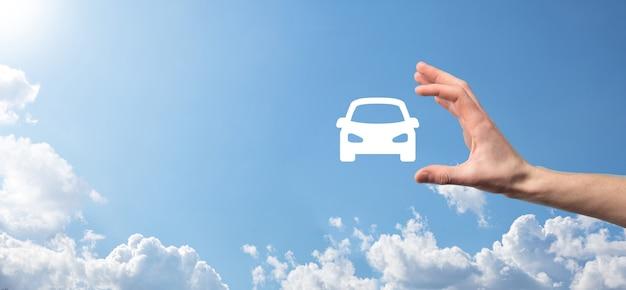 Męskiej ręki trzymającej samochód auto ikona na niebieskim tle. szeroka kompozycja banerowa. koncepcje ubezpieczenia samochodu i zrzeczenia się szkód powypadkowych