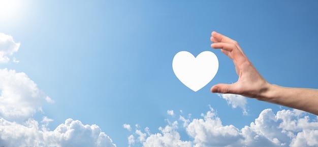 Męskiej ręki trzymającej serce, jak ikona na niebieskim tle. życzliwość, miłość, czysta koncepcja miłości i współczucia. baner z miejsca na kopię.