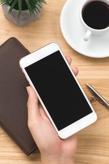 Męskiej ręki trzymającej smartfon z notebookami, długopisem i filiżanką kawy obok na drewnianym stole w godzinach porannych