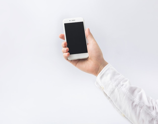 Męskiej ręki trzymającej smartphone, mobilny na białym tle.