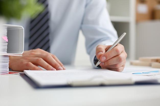 Męskiej ręki trzymającej srebrny długopis gotowy zrobić notatkę