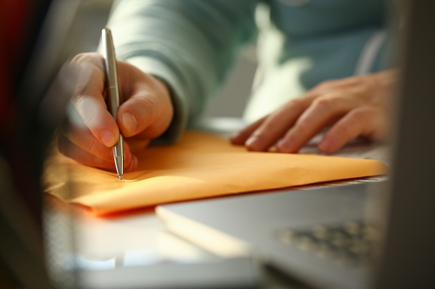Męskiej ręki trzymającej srebrny długopis