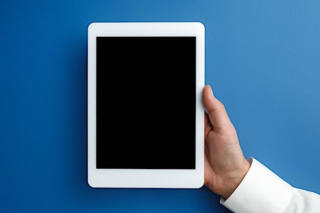 Męskiej ręki trzymającej tablet z pustym ekranem na niebiesko