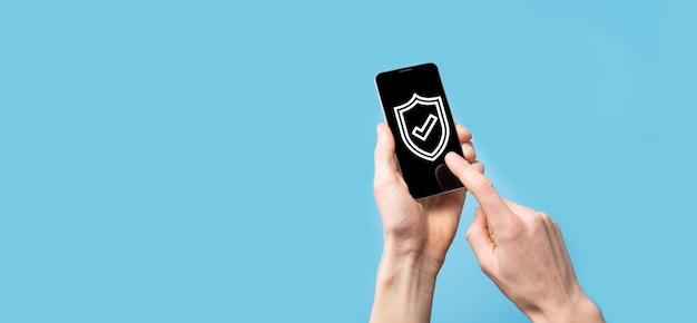 Męskiej ręki trzymającej tarczę ochronną z ikoną znacznika wyboru na niebieskim tle. ochrona komputera bezpieczeństwa sieci i bezpieczna koncepcja danych.