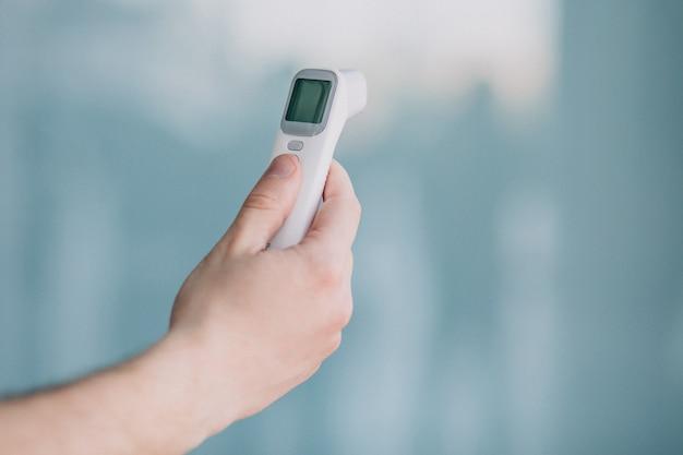 Męskiej ręki trzymającej termometr elektryczny