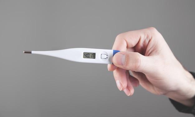 Męskiej ręki trzymającej termometr. wysoka temperatura
