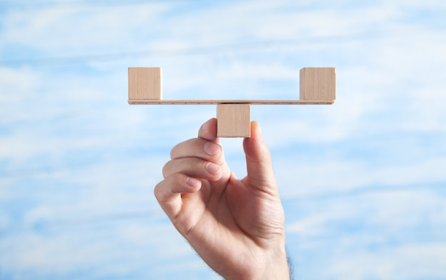 Męskiej ręki trzymającej wagi równowagi wykonane z drewnianych kostek.