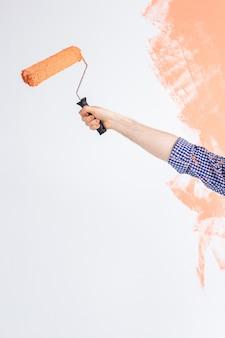 Męskiej ręki trzymającej wałek do malowania zanurzone w kolorze pomarańczowym przed zieloną ścianę. skopiuj miejsce.