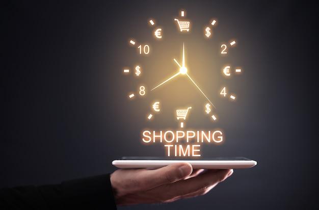 Męskiej ręki trzymającej zegar. czas zakupów. zakupy online