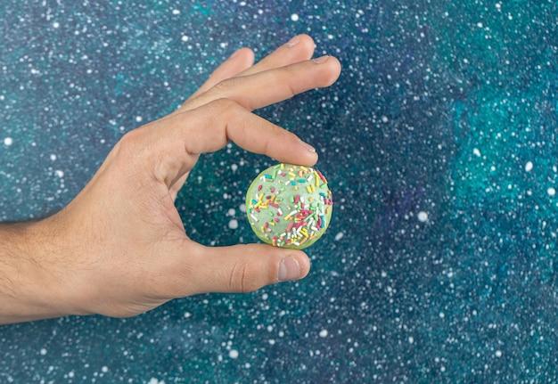 Męskiej ręki trzymającej zielone ciastko z kolorowymi cukierkami.