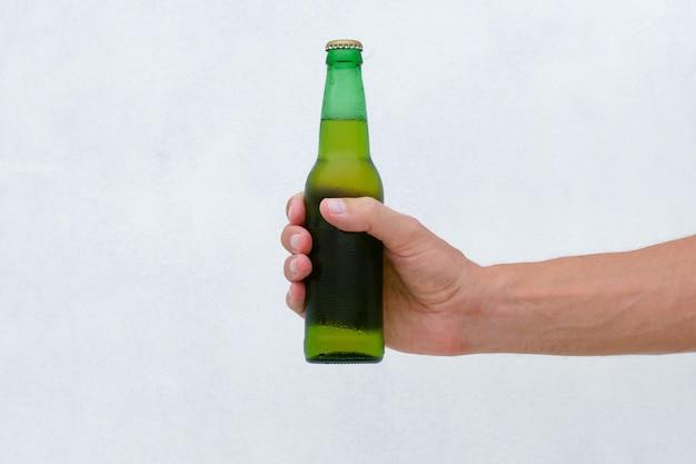 Męskiej ręki trzymającej zimną butelkę piwa. styl życia.