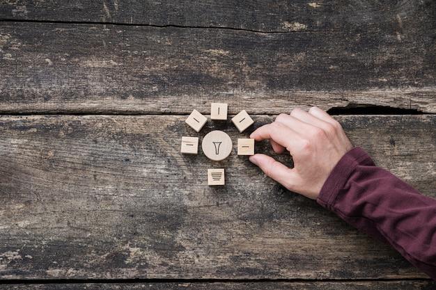 Męskiej ręki tworzenie kształtu żarówki z drewnianych klocków w koncepcyjnym obrazie innowacji i idei.