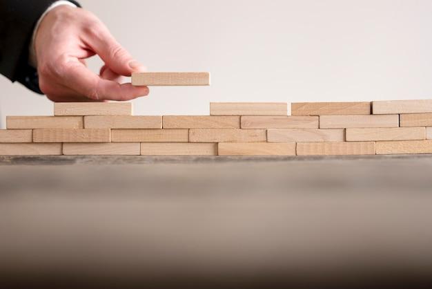 Męskiej ręki ukończenie budowy ściany z drewnianych cegieł na stole, kopia przestrzeń.
