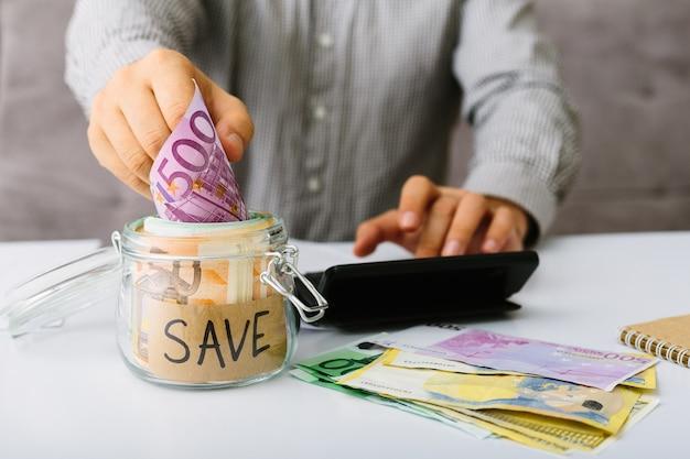 Męskiej ręki umieszczenie banknotów banknotów euro w szklanym słoju do oszczędzania