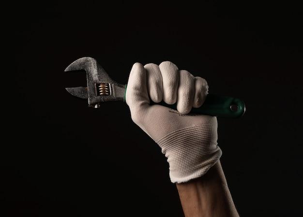 Męskiej ręki w rękawiczkach trzymając narzędzie klucza z bliska na czarnym tle.