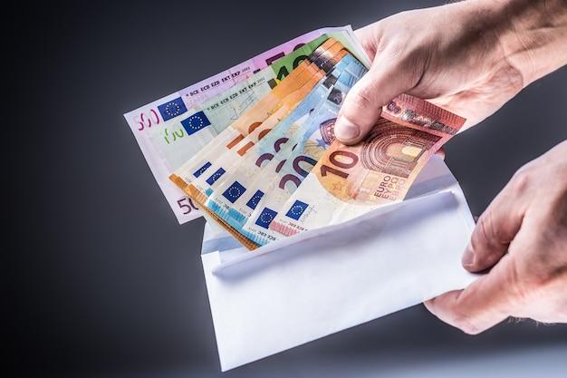 Męskiej ręki włożona do koperty banknotów euro - koncepcja łapówki i korupcji.