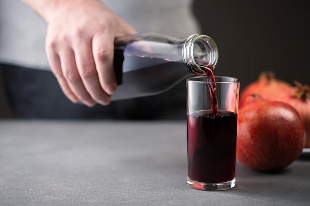 Męskiej ręki wylewanie soku z granatu z butelki do szklanki