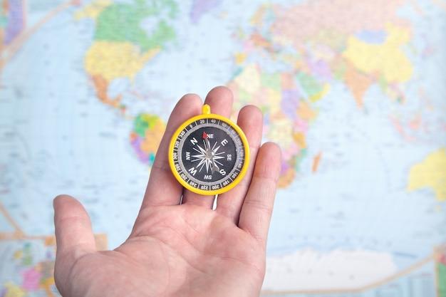 Męskiej ręki wyświetlono kompas na tle mapy świata.