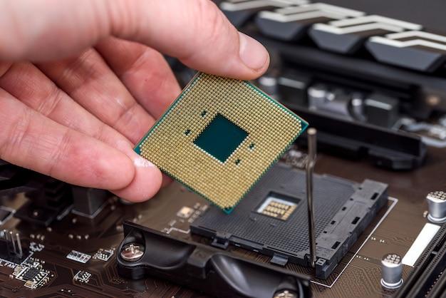Męskiej ręki zdejmując chip procesora z płyty głównej